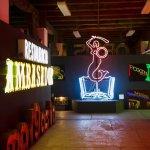 Gang met neonlampen in de vorm van de sirene van Warschau in het Neon Museum
