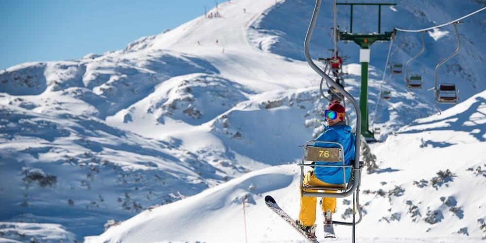 Skiër op een skilift tussen besneeuwde bergen in Slovenië