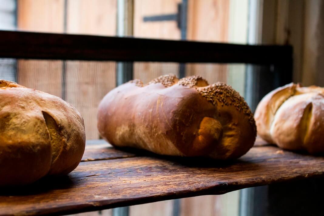 Ambachtelijke broden op een houten plank in het bakkerijmuseum van Hattem, een van de Nederlandse Hanzesteden