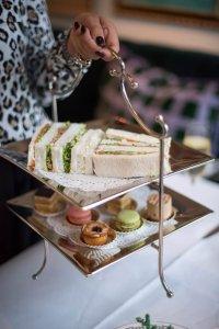 Etalagère met sandwichs, macarons en taartjes voor de Afternoon Tea in Hotel Van Cleef