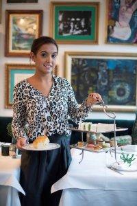 Vrouw met een bordje scones en een etalagère met sandwichs, macarons en taartjes voor de Afternoon Tea in Hotel Van Cleef