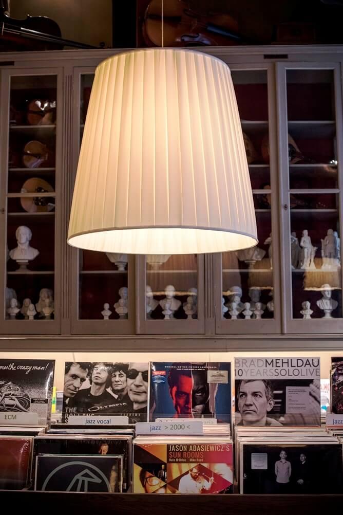 Witte lampenkap en tafel met LP's en kast met beeldjes in Rombaux Brugge