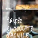Glazen vitrine met 'triple chocolate brownie' op geschreven en taart binnenin