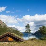 Uitzicht op het Gjendemeer in Noorwegen met een huisje met een vegetatiedak