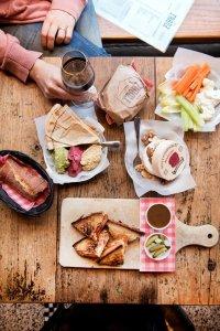 Bovenaanzicht van een lunch met hummus, cheeseburger, croque planchette, groentjes en camembert bij Chez Franz in Brussel