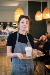 Serveerster van Ici met een plateau met een latte macchiato