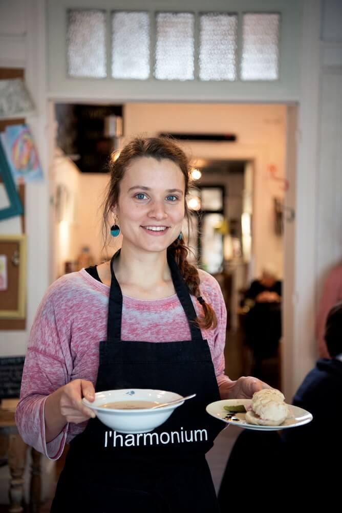 Serveerster met een zwarte schort van L'harmonium met een bord soep en bord met een broodje