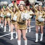 Cheerleaders in gouden kleren in de St. Patrick's Day parade