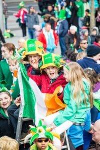 Verklede kinderen met de Ierse vlag kijken naar de St. Patrick's Day parade