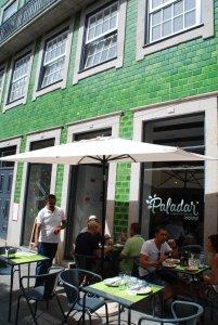 Het terras met parasol en de gevel met groene tegels van Paladar in Porto