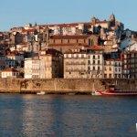 Koppel aan een tafeltje naast de Douro in Porto met uitzicht op Ribeira