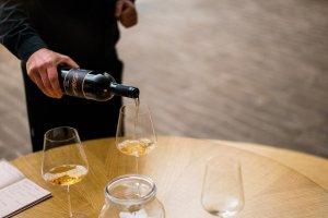 Wijnglazen die ingeschonken worden met oranje wijn