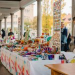 Kleurrijke kraampjes met souvenirs in een zuilengang in Ljubljana