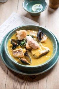 Een bord met vis en schelpdieren in een gele saus