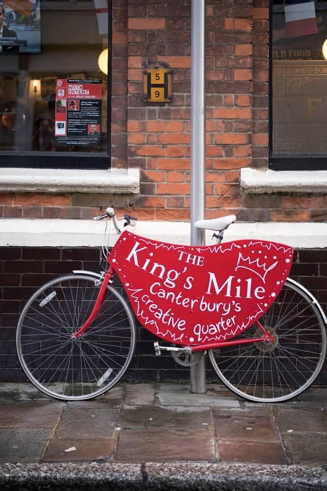 """Geparkeerde rode fiets met reclame voor the King's Mile Canterbury """"creative quarter"""""""