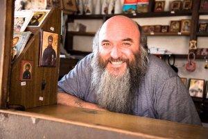 Man met baard achter de toog van een iconenwinkeltje