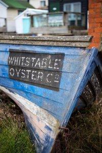 """Oude houten bootje met """"Whitstable Oyster Co"""" op de boeg"""