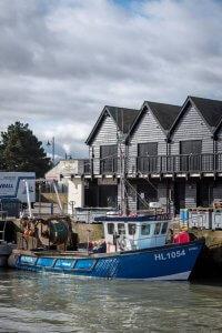 Een vissersbootje aan de kade met 3 oude vissershuisjes