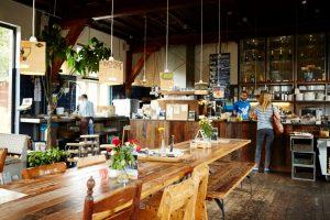 Interieur van lunchbar De Bakkerswinkel met houten tafels