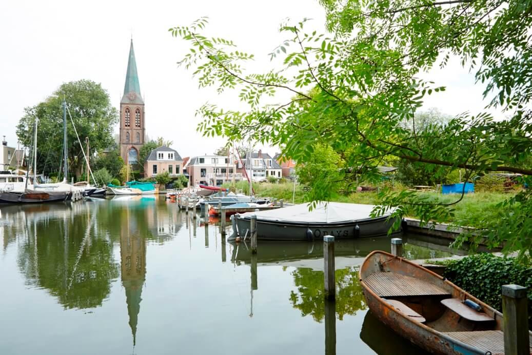 Water met bootjes, kerk en vissershuisjes in de achtergrond