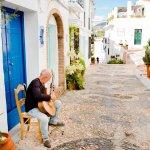 Man speelt gitaar voor zijn deur in Frigiliana, Costa del Sol