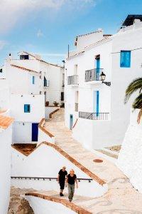 Hellend straatje met witte huizen en blauwe deuren en luikjes