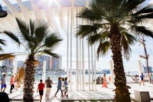 Uitzicht langs twee palmbomen op de dijk en zee in Málaga, Costa del Sol