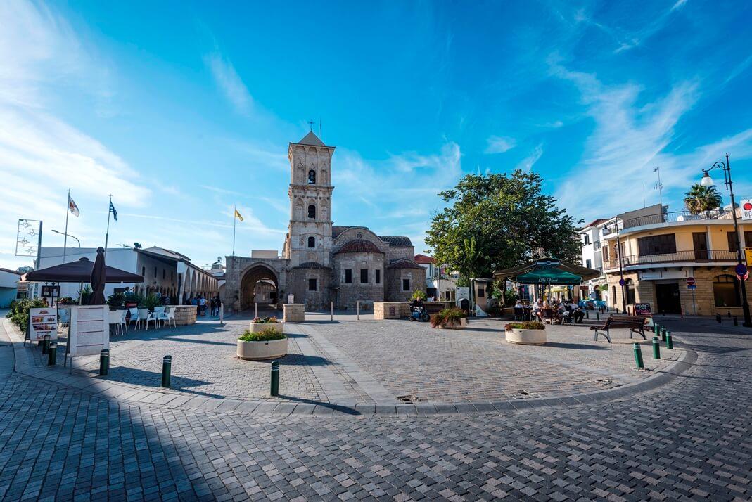 Stadsplein van Larnaka met gebouwen en toren.