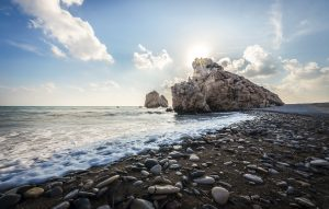 Strand met een rots waar de zon achter verdwijnt