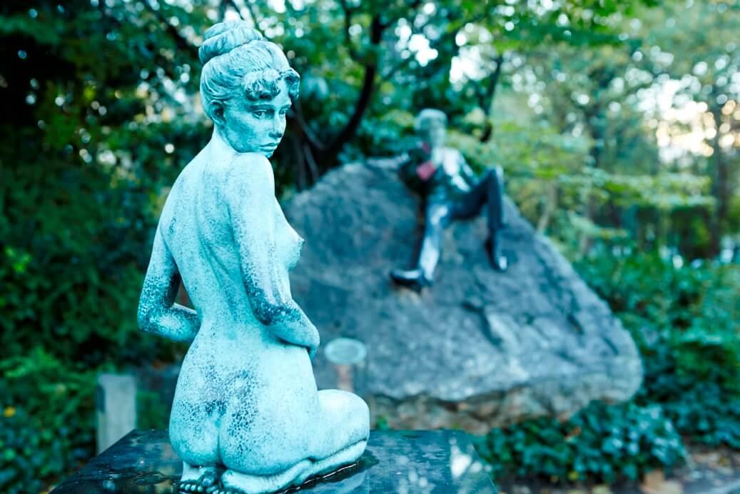 Bronzen beelden van Oscar Wilde op een rots en zijn vrouw