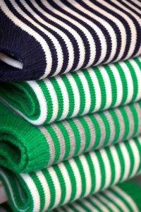 Stapel opgevouwen gestreepte truien van Le Tricoteur in Guernsey