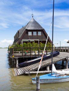 Houten woning met rieten daken op een meer met een aangemeerd bootje