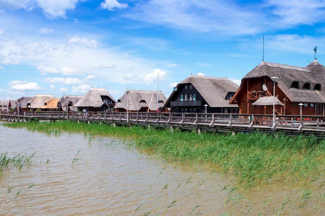 Houten woningen met rieten daken op een meer