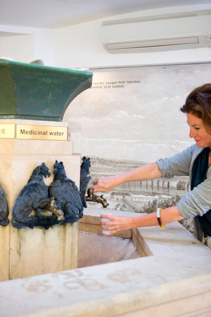 Een vrouw die een plastic bekertje vult aan een versierde kraan