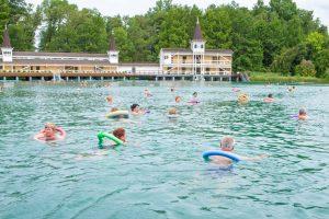 Zwemende mensen met zwembanden in een meer
