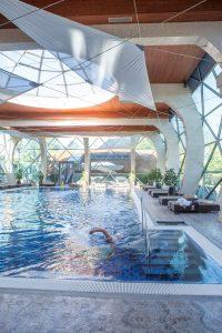 Binnenzwembad met zwemmer en ligzetels