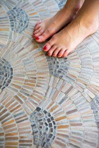 Twee vrouwenvoeten met rode nagellak op een mozaïekvloer