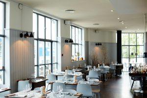 Restaurantzaal met lichtblauwe stoelen en gedekte tafels