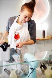 Vrouw met schort giet iets uit een kruik in een mixer