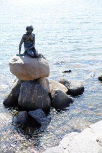 Bronzen beeld van de Kleine Zeemeermin op een rots in het water in Kopenhagen