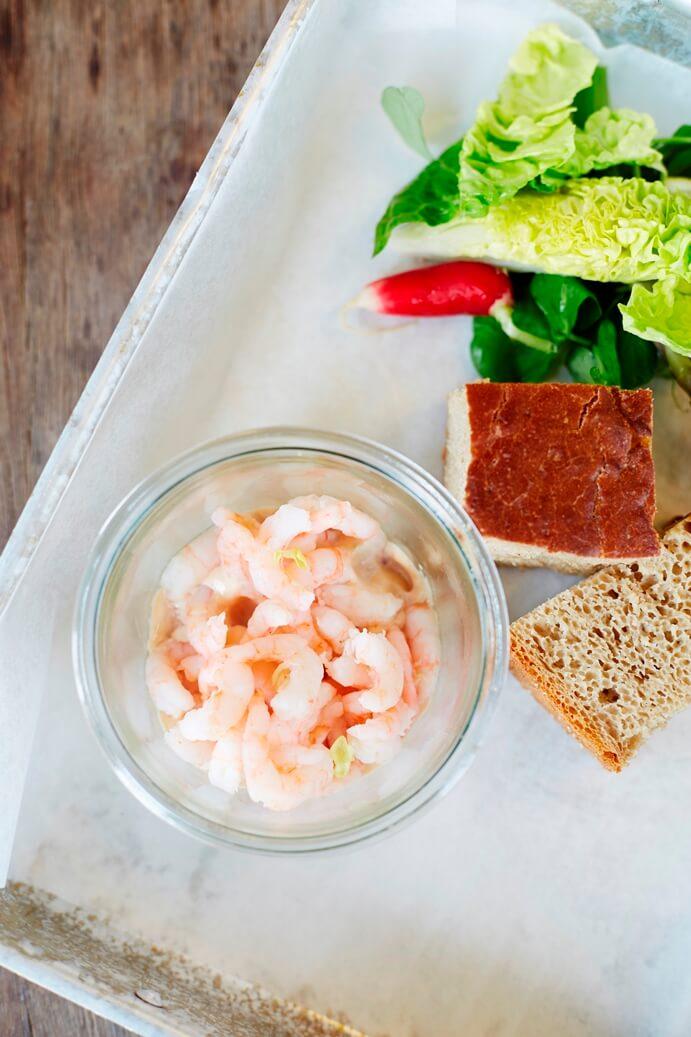 Bord met slaatje, kommetje grijze garnalen en brood