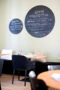 Het interieur van Gust in Kortrijk. Zwarte stoelen en lichte tafels en muur met ronde krijtborden.