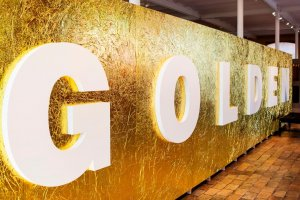 """Gouden muur met """"Golden"""" in witte letters in Texture, Kortrijk"""