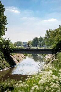 Fietser over een brug op de route van de fietstocht Lokaal Lekkers rond Kortrijk
