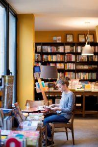 Zittende vrouw met boek in een boekenwinkel