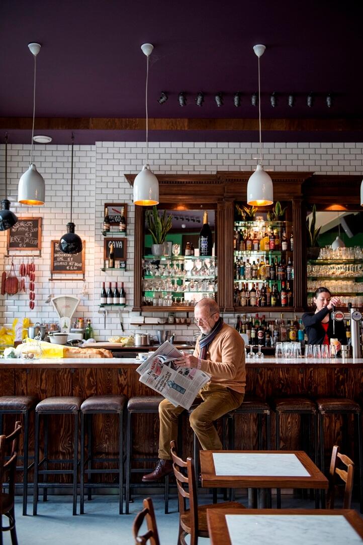 Man leest krant aan de bar van Leuven Central