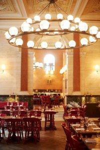 Restaurant met houten stoelen en tafels en kroonluchter met ronde lampen