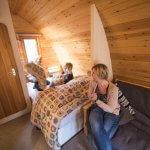 Binnenkant van een logeerpod met tweepersoonsbed en zetel in Berdorf