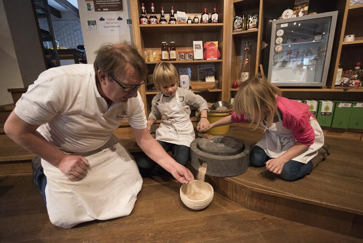Man en twee kinderen malen graan in Heringer Millen, Luxemburg