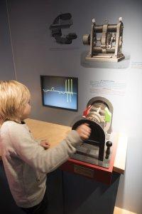 Jongen draait aan een museumobject i.v.m. elektriciteit in het Henri Tudor museum in Rosport